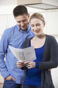 Happy Couple Looking At Details For Property They Hope To Buy
